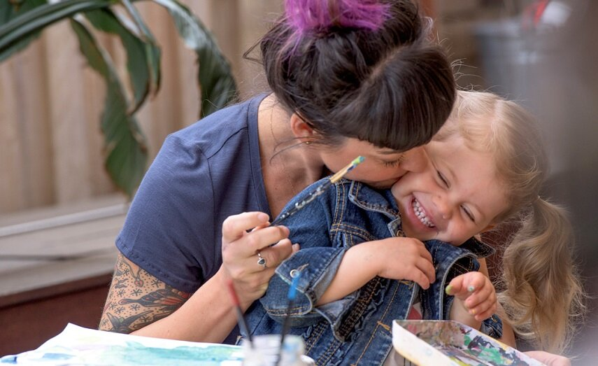 Mother kissing daughter whilst painting together