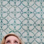 Image of patterned wall tiles with woman staring at the sky