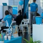 Bupa wellbeing expo with people receiving massages, smoothie stand and health consultations