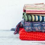 Warm woven scarves of bright colours lying in stack on wooden table